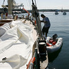 Mario Swainson, a crew member aboard the Spirit of Bermuda, lowers himself into an inflatable boat to travel around Gloucester Harbor yesterday. The boat, which is docked in East Gloucester, is spending a couple days here before heading to Sail Boston on Wednesday. Photo by Kate Glass/Gloucester Daily Times Monday, July 6, 2009
