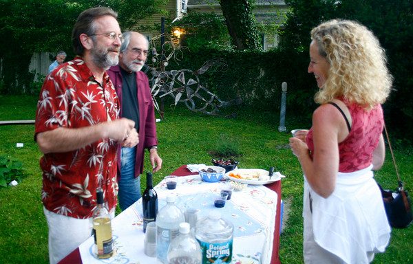 Gloucester: Graig Brooks, one of the owners of Flatrocks Gallery and bookstore, and Cliff Post, center, talk to Brenda Treuhaft during an exhibition opening featuring interpretations of maps, landscape and art of local artists on Friday night. <br /> Silvie Lockerova/Gloucester Daily Times