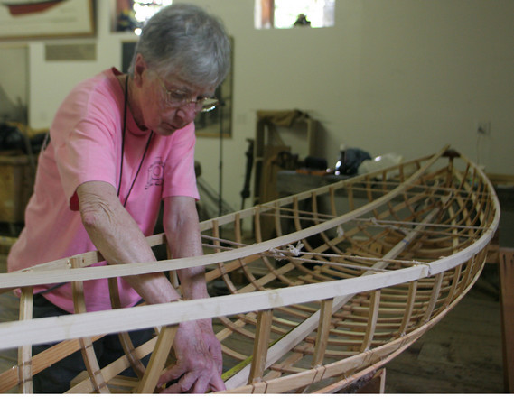 Eileen Ford of Rockport measures of the bottom of her canoe before cutting and placing the floorboards in it.  Ford has been taking a week long class on canoe building at the Essex Ship Building Museum. Photo by Maria Uminski/ Gloucester Daily Times