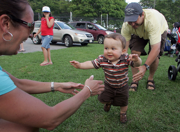 Gloucester: Connor Oliveira, 11 months, works on taking his first steps as he walks from his dad, Mark, into the arms of his mother, Ann Marie, at Boudreau Field Saturday evening. Connor and his parents came to the field watch his cousins play in the little league game held that night. Mary Muckenhoupt/Gloucester Daily Times