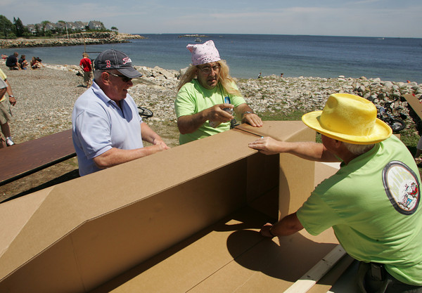 Rockport: From left, Tom Winter, Dana Griffin, wearing a blonde wig, and Eric Bergengren work on their cardboard boat during the annual Race to the Bottom boat race put on by the Tyrian-Ashler-Acacia Lodge at Back Beach Saturday. Only certains items, such as 2 pieces of cardboard, duct tape, 25 feet of string, a yard stick, two pieces of wood and a razor knife can be used in the construction of the boat that must only take two hours to build. Mary Muckenhoupt/Gloucester Daily Times