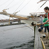 Gloucester: Tim Camille, 13, right, Zachary Burke, 13, center, and Jonathan Gray, 12, left, all of Gloucester, fish off the State Fish Pier next to the tall ship Europa yesterday afternoon. Tim said all he had caught were two crabs, but thinks he probably caught the same one twice. Photo by Kate Glass/Gloucester Daily Times Tuesday, July 7, 2009