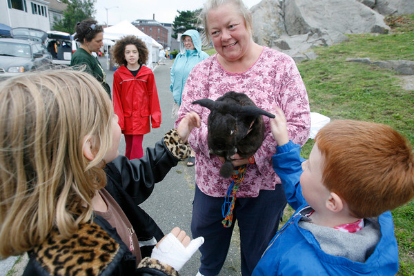 Gloucester: Cindy Churchill lets Lilith Tempest, 7, left, and Ari Dimond-Putnam, 5, right, pet her rabbit, Midnight, at the end of the Farmers Market on Thursday. Churchill takes Midnight for walks on the Boulevard every day, but he also likes the Farmers Market for extra greens. Photo by Kate Glass/Gloucester Daily Times Thursday, July 23, 2009