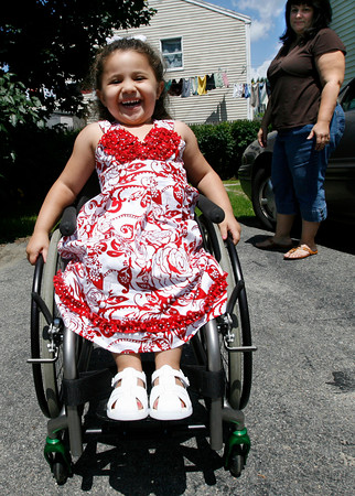 Gloucester: Olivia Curcuru, 3, spins around her grandmother's driveway as her mother, Carolyn Curcuru, watches. Olivia, who was born in Gloucester and now lives in Arizona, was paralyzed from the waist down as the result of an accident earlier this year, but refuses to let that slow her down. Photo by Kate Glass/Gloucester Daily Times Monday, July 13, 2009