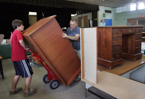 Manchester: Graham Shaw, 15, a student at Manchester Essex High School helps his dad Dave move a desk from the school cafeteria during the Manchester Essex High School Yard Sale Saturday morning. Mary Muckenhoupt/Gloucester Daily Times
