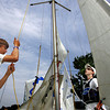 Gloucester: Nick Hanna, 15, raises the sail of his 420 sialboat with some help from his friend Ben MacShane, 12, right, as Nick gets ready for the 108th annual Squam Day sailing races at Annisquam Yaught Club Friday morning.  Mary Muckenhoupt/Gloucester Daily Times