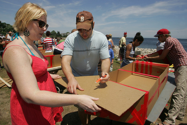Rockport: Erika Batchelder and Mike Palladino work on their cardboard vessel for the Race to the Bottom boat race at Back Beach Saturday. Only certains items, such as 2 pieces of cardboard, duct tape, 25 feet of string, a yard stick, two pieces of wood and a razor knife can be used in the construction of the boat that will hopefully stay afloat.  The Tyrian-Ashler-Acacia Lodge held this fund raising event and each year it attracts more builders and spectators .Mary Muckenhoupt/Gloucester Daily Times