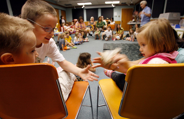 Gloucester: Rose Groleau, 2, passes a bird leg to her brothers, Charlie, 4, and Sam, 6, during the Audubon Ark Birds of Prey program at the Sawyer Free Library yesterday morning. Attendees got to see a screech owl, broadwing hawk, and great horned owl. Photo by Kate Glass/Gloucester Daily Times Monday, July 6, 2009