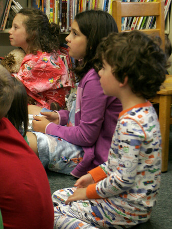 "From left to right: Paige Mandia, 7, of Beverly, Rebecca Braimon, 9 and Brady Friedrich 4 1/2 both of Essex listen to the story of ""One Duck Stuck"" during the pajama party at the TOHP Burnham Essex library last night. Maria Uminski/ Gloucester Daily Times"