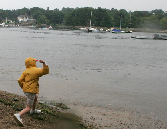 William Locke, 9, of Manchester skipped rocks during the rain showers yesterday while he waited to hear whether or not he would have his boating lesson at Tuck's Point. Photo by Maria Uminski/ Gloucester Daily Times