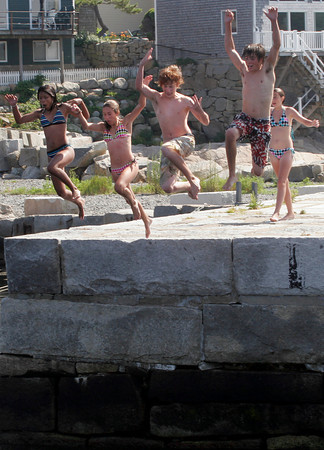 Rockport: Sedra Baldarini, Maddie Sanfilippo, Henry Gates, John Pereira, and Marissa Foote, all of Rockport, leap off Lumber Wharf as they try to cool off yesterday afternoon. Photo by Kate Glass/Gloucester Daily Times Tuesday, July 28, 2009