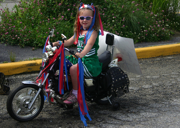 Manchester: Catherine Garlitz, 7, rides her motorcycle in the Manchester  4th of July parade Saturday morning. Silvie Lockerova/Gloucester Daily Times