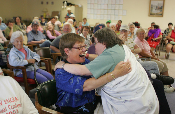 """Gloucester: Nancy Gagne, left, hugs her friend Janice Cook after Cook and Ron Pool performed """"Ally Oop"""" at Day by Day adult daycare center in Gloucester Wednesday afternoon. Day by Day held thir Senior Idol contest where people who go to the facilty could perform and get reviewed by judges.  Mary Muckenhoupt/Gloucester Daily Times"""