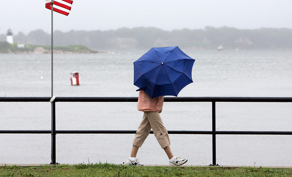 Gloucester: Jane Johnson shields herself fromt he wind and rain while walking Stacy Boulevard Friday afternoon. Mary Muckenhoupt/Gloucester Daily Times