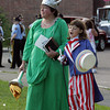 Gloucester: Faithe Shatford, 8, sings a song while standing with her mom Michelle as they wait to walk in the Horribles Parade Friday evening. Mary Muckenhoupt/Gloucester Daily Times
