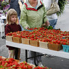 Mackenzie Ciolino, 6, and Josephine Ciolino check out the strawberries from Cider Hill Farm at the Cape Ann Farmers' Market yesterday afternoon. Despite the rain, many people turned out for the opening day. Photo by Kate Glass/Gloucester Daily Times Thursday, July 2, 2009