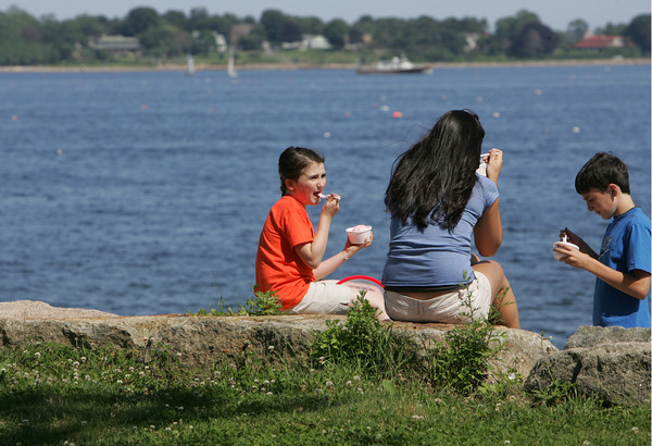Gloucester: Emily Whitmore, 9, and her brother John, 12, enjoy an ice cream and a scenic view of Gloucester Harbor with their babysitter Samantha Rose at Stage Fort Park Friday afternoon. Mary Muckenhoupt/Gloucester Daily Times