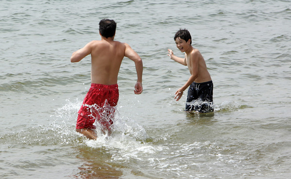Gloucester: Sam Sobell, 12, tries to spash his dad, Steve, while playing in the water at Niles Beach Saunday afternoon. Mary Muckenhoupt/Gloucester Daily Times