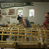 From left to right, Hilary Russell, Ben Wildrick and Jim Watson are busy at work waterproofing their double paddled canoes with a coat of polyurethane before they move on to their next step. The group has been taking a week long class on canoe building at the Essex Ship Building Museum. Photo by Maria Uminski/ Gloucester Daily Times