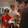 Harry Schlitz, owner of Sorrel, an Alaskan Husky, looks on while Michael Murphy, 5, and sister Sarah Murphy, 9, of Rockport pet him after a demonstration about sled dogs at the Rockport Public Library. Sorrel, along with two other dogs, Su and Pixie, are part of a sled dog educational and therapy program, Mountain Mushers, which travels across the country. Photo by Maria Uminski/ Gloucester Daily Times