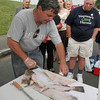 Steve Parkes gives a tutorial on how to fliet a whole fish in the Community Supported Fisheries at the Cape Ann Farmers' Market yesterday in Gloucester. The tutorial was done to help guide people who recieved fish from the CSF program because the fish is given out whole. Photo by Maria Uminski/ Glouester Daily Times