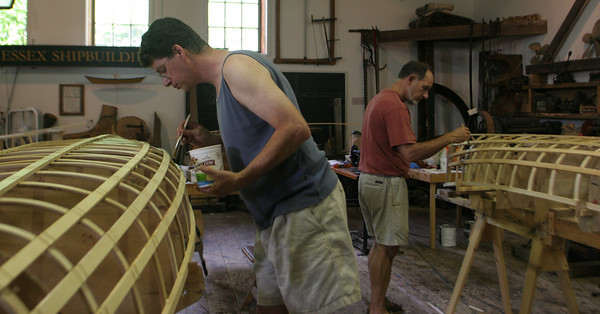 From left to right: Ben Wildrick and Jim Watson of Gloucester work diligently on waterproofing their double paddled canoes during a week-long class at the Essex Ship Building Museum. Photo by Maria Uminski/ Gloucester Daily Times