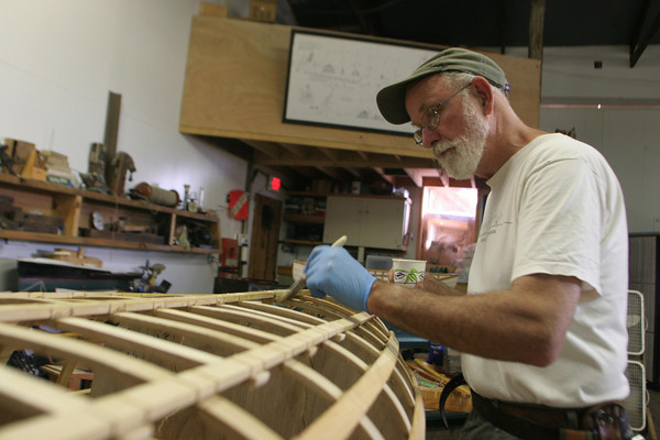 Hilary Russell of Sheffield lends a hand waterproofing a double paddled cannoe with polyurethane during the week long class he teaches on building cannoes. The class took place at the Esexx Ship Building Museum. Photo by Maria Uminski/ Gloucester Daily Times