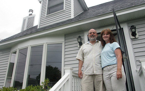 Gloucester: JoAnn and Peter Trimmins stand in front of their recently rehabilitated home on Eastern Avenue Thursday morning. The Trimmons' home was severly damaged after the home of their neighbor, Wayne Sargent, exploded. Mary Muckenhoupt/Gloucester Daily Times