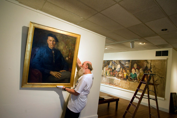 Gloucester: Facilities manager Paul Miller hangs a painting by Rockport artist Marguerite Pearson of Aldro Hibbard for the show Art is Long, Life is short: Rockport Artists in the 1930s at the Cape Ann Museum Thursday morning. Mary Muckenhoupt/Gloucester Daily Times.