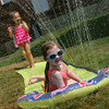 Gloucester: Ila Bernard, 5, slides on a slip 'n slide with her cousin Julia Carrancho, 3, while having a good time cooling off at their Grammy's house on Washingotn Street Friday afternoon. Mary Muckenhoupt/Gloucester Daily Times