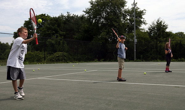 Manchester: Evan Fitzgerald, Anton Kozyrev, and Alanna Fitzgerald practice returning the ball during tennis lessons at the Brook Street Tennis Courts yesterday morning. The lessons are offered by the Manchester Parks & Recreation Department. Photo by Kate Glass/Gloucester Daily Times
