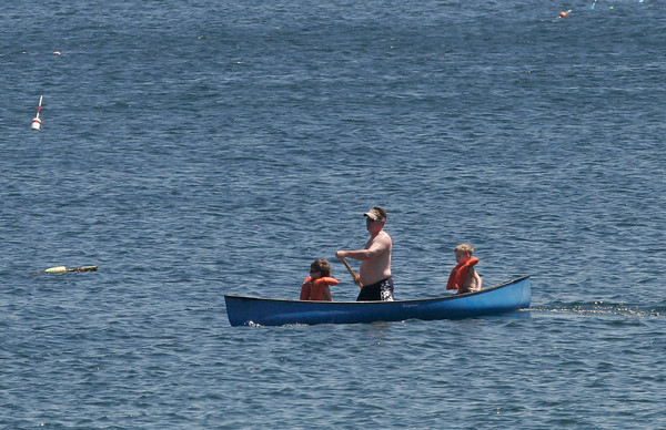 Rockport: Jon Jones paddles around Back Beach with his sons, Ian, 5, and Colin, 7. They found the canoe in their grandfather's yard and wanted to see if it still worked. Photo by Kate Glass/Gloucester Daily Times