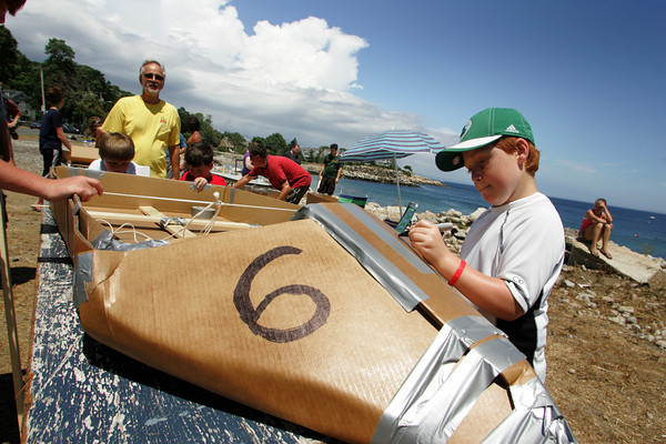 Rockport: Ben Yanakakis, 9, draws a number six on the cardboard boat he built with his family for the annual Race to the Bottom at Back Beach Saturday afternoon.  The race, put on by the Tyrian-Ashler-Acacia Lodge as a fundraiser, requires its participants to build a boat using only certain items such as cardboard, a 25 ft. rop, duct tape, and a can of schalak. Ten boats were in this years race and all but a few didn't make it. Mary Muckenhoupt/Gloucester Daily Times