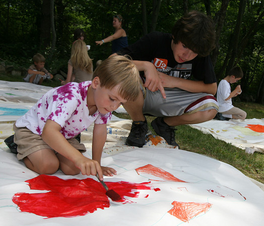 Rockport: Myles Wrinn gives Wyatt Rose, 6, some advice as he paints a self portrait from a body tracing at Art Harbor Camp at Windhover. Photo by Kate Glass/Gloucester Daily Times