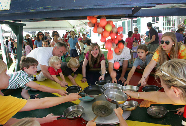 Gloucester: Kids and adults wait for the balls to drop while playing pan handler at the Annisquam Village Seafair Saturday. The rule is to keep one hand on the pan and one hand behind your back when catching the balls for points. Mary Muckenhoupt/Gloucester Daily Times