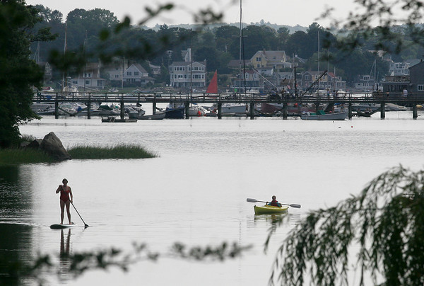 Gloucester: A paddleboarder and kayaker make their way around the calm water at Lobster Cove yesterday afternoon. Photo by Kate Glass/Gloucester Daily Times