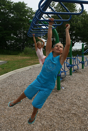 Gloucester: Sabella Curcuru, front, and Jolie Frontiero, both of Gloucester, climb across the monkey bars at Stage Fort Park on Tuesday morning. Photo by Kate Glass/Gloucester Daily Times