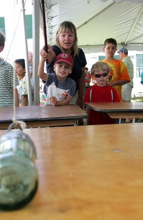 Gloucester: Wyatt Rose, 6, gets some help from his mom Melissa as he tries to get the ring around the bottle to get the bottle to stand up at one of the kids game during the Annisquam Village Seafair Saturday.  Standing  right is Wyatt's twin brother Jasper. Mary Muckenhoupt/Gloucester Daily Times