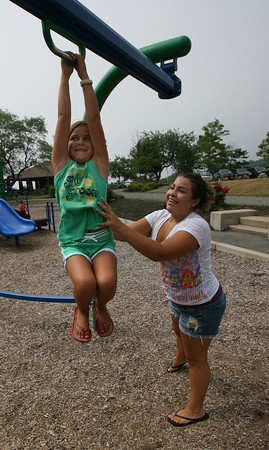Gloucester: Racquel Shaw gives Angelena Curcuru a push so she can ride the zip line at Stage Fort Park Tuesday morning. Angelena was too short to grab the handle so she got a boost from Racquel. Photo by Kate Glass/Gloucester Daily Times