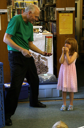 """Essex: Anna Mayer waits to see if magician Steven Rudolph can successfully """"recycle"""" items into something new during the """"Going Green Magic Show"""" at the TOHP Burnham Library on Wednesday evening. Photo by Kate Glass/Gloucester Daily Times"""