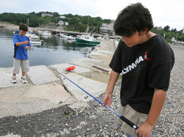 Rockport: Christian Wright, 11, holds his fishing rod steady as his friend, Jameson Kamm, 11, fixes the line as they try their luck off Granite Pier on Tuesday afternoon. Jameson was hoping to catch stripers, while Christian said he'd be happy to catch anything. Photo by Kate Glass/Gloucester Daily Times