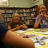 Manchester: Haley New, left, and Alexa New giggle while making beads using strips of old magazines at the Manchester Public Library on Monday afternoon. The girls used the beads to make a bracelet. Photo by Kate Glass/Gloucester Daily Times