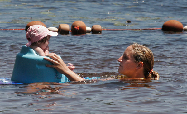 Essex: Kim Bouchie of Gloucester swims with her daughter, Madelyn Lane, 4 months, at Chebacco Lake on Thursday afternoon. Bouchie says she prefers the lake to the ocean because it is warmer and they can stay in the water longer. Photo by Kate Glass/Gloucester Daily Times