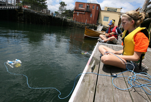 Gloucester: Kerri Colby and  Fulton Randge-Cunha maneuver their remote operated vehicles through the water behind the Gloucester Maritime Heritage Center during a two-week science camp. The kids built speakers and designed and programmed video games at MIT and built ROVs at the heritage center. Photo by Kate Glass/Gloucester Daily Times