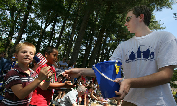 Manchester: Matt Hoyle hands out flags from the Manchester Community Center to Kevin Harding, left, and Jack Ashley during the Manchester 4th of July Parade yesterday afternoon. Photo by Kate Glass/Gloucester Daily Times