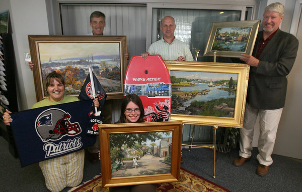 Gloucester: Clockwise from top left: Peter Webber, Tim Burton, Bob Hastings, Katie Eastman and Susan Lucas show off several of the items up for bid at the Cape Ann Chamber of Commerce Auction at Cruiseport on Friday night. The items include paitings by Robert Gruppe, Don Mosher and Ken Knowles as well as sporting goods merchandise and autographed items from local sports teams. Photo by Kate Glass/Gloucester Daily Times
