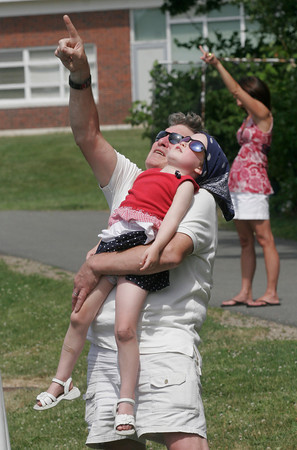 Manchester: David Perkins holds his granddaughter, Grace Perkins, 4, as they watch the skydivers land on Coach Ed Field Field yesterday afternoon following the Manchester 4th of July Parade. Photo by Kate Glass/Gloucester Daily Times