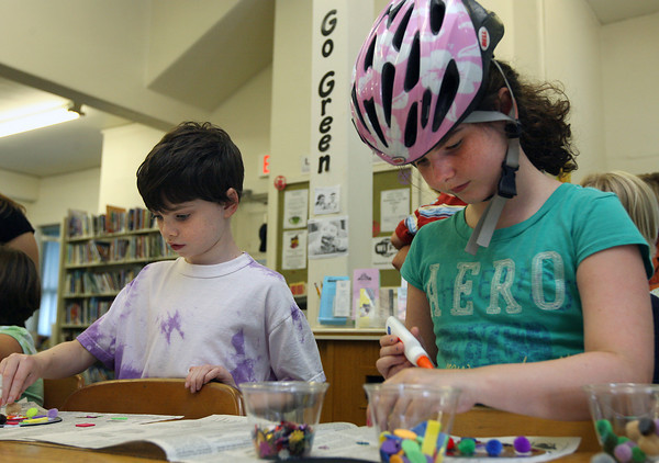 Essex: Olivia Soulard and her brother, Ben, make coasters from recycled CDs during Green Craft Time at the TOHP Burnham Library on Tuesday. The two rode their bikes to the library and Olivia left her helmet on while crafting. Photo by Kate Glass/Gloucester Daily Times