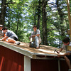 Essex: Jeremy Pratt, 17, going for his Eagle Scout badge, looks over as his friends help him replace the roof of a storage shed at Centennial Grove Saturday afternoon. Pratt's Eagle Scout project, which must be a 100 hour community service project, is to replace the roof as well as give the shed a complete paint job. Also pictured, from left, Life Scouts Michael McCollum and Sean O'Donnell and Eagle Scout Danny White, right.