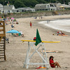 Rockport: Lifeguard Brittany Peterson sits in fornt of her lifeguard chair which waves the green flag for safe swimming at Long Beach Thursday morning.For the first time in Rockport beaches now have a color-coded swimming flag system along with lifeguards at its beaches. Green is safe to swim, yellow is swim at your own risk and red indicated swimming is prohibited.  Mary Muckenhoupt/Gloucester Daily Times